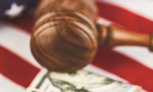 Gavel with American dollars and US flag on wooden desk